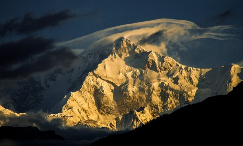 mountain peak covered in snow with morning sunlight on one side himalayas india