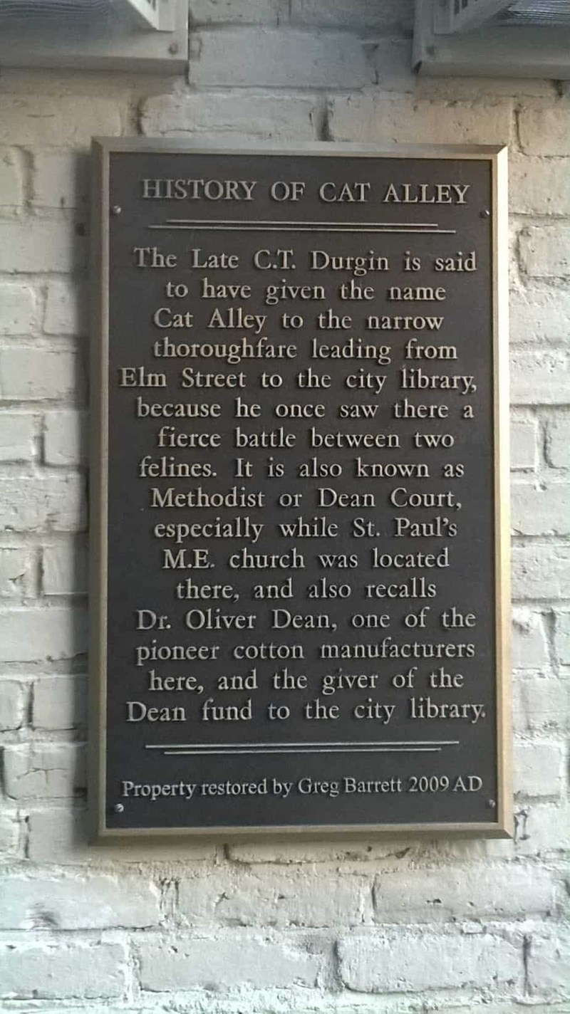 Commemorative plaque - HISTORY OF CAT ALLEY The Late C.T. Durgin is said to have given the name Cat Alley to the narrow thoroughfare leading from Elm Street to the city library, because he once saw there a fierce battle between two felines. It is also known as Methodist or Dean Court, especially while St. Paul's M.E. church was located there, and also recalls Dr. Oliver Dean, one of the pioneer cotton manufacturers here, and the giver of the Dean fund to the city library Property restored by Gre