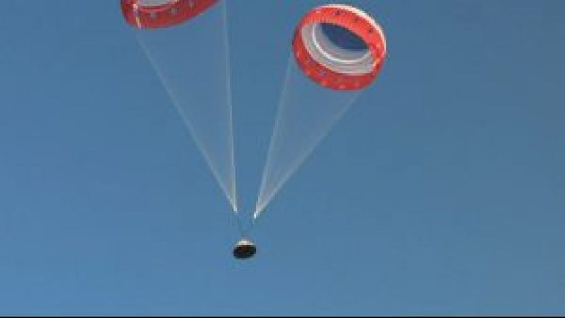 picture starliner capsule with two parachutes in air