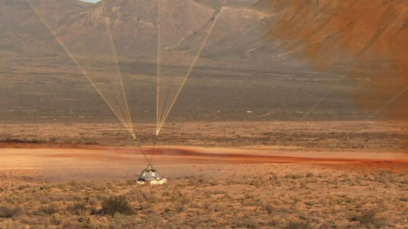 picture starliner capsule landing in new mexico desert with parachutes attached to it