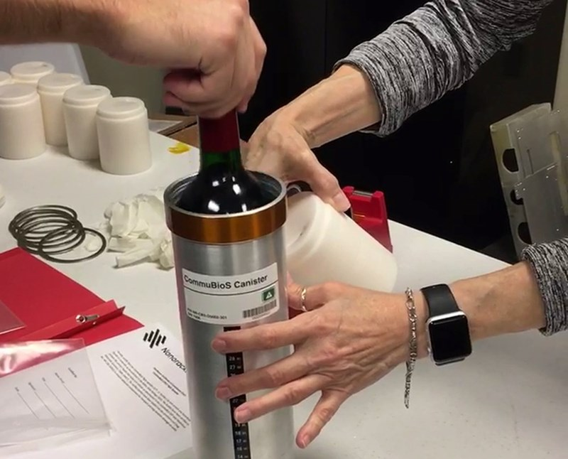 picture bottle red wine being put into metal flask for ageing in space