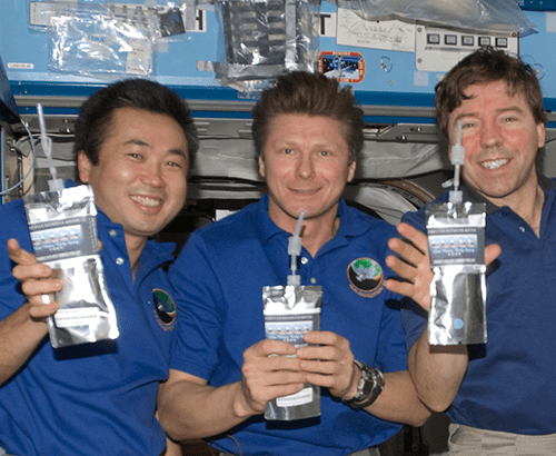 picture three male astronauts in international space station holding silver packets of food