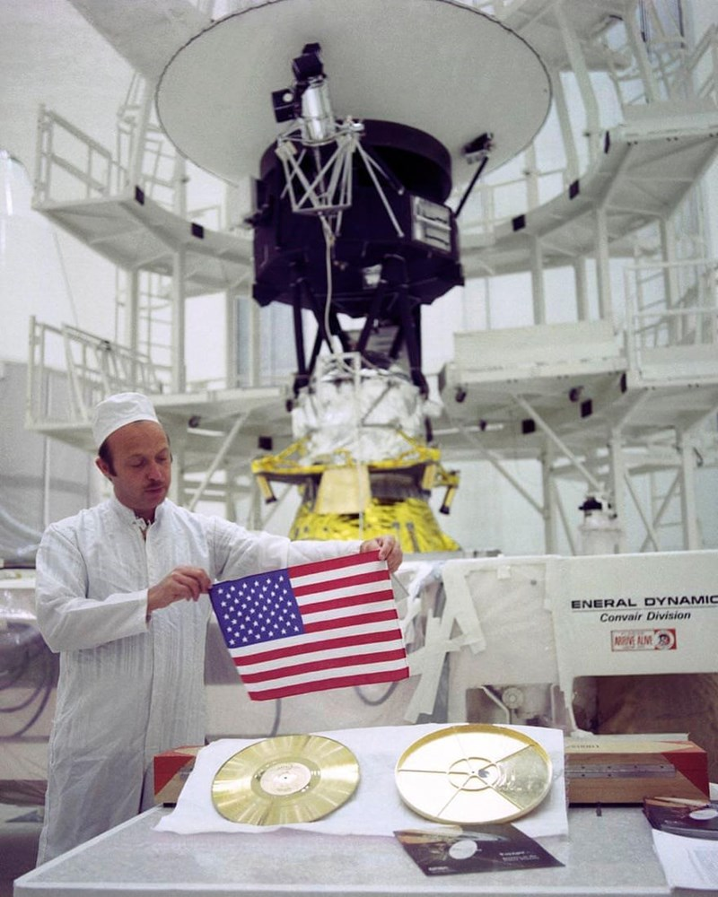 man holding up small american flag with gold disk in front of voyager 2