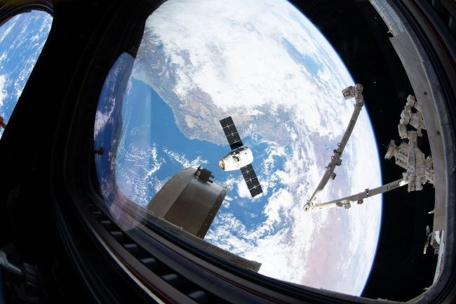 photo robot arm reaching out from international space station to grab dragon cargo ship