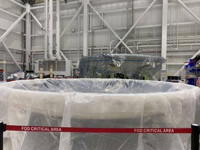 boeing's first starliner capsule covered in plastic in factory
