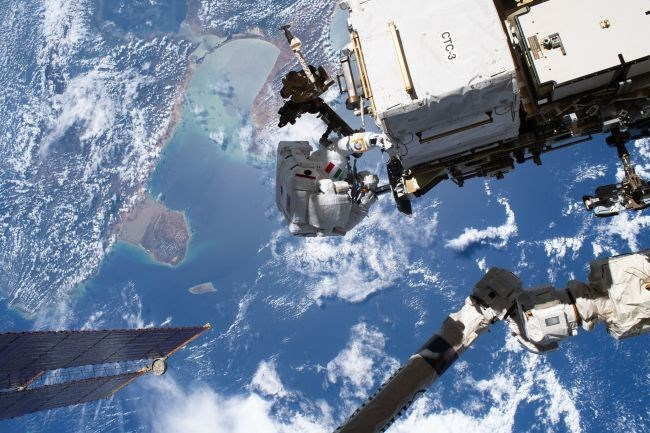 two astronauts repairing cosmic ray detector on international space station above the earth seas blue