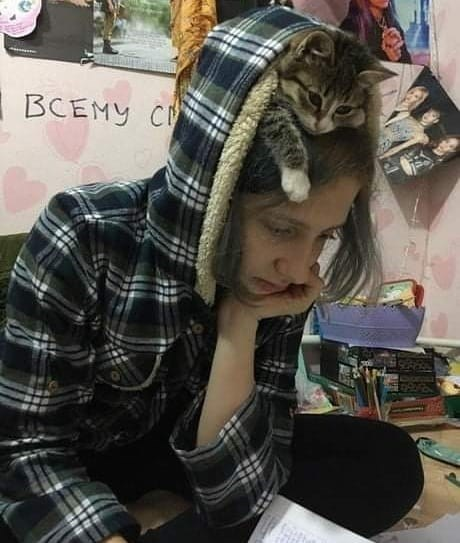 woman sitting on the floor looking concentrated on something she's reading, the hood of her jacket is pulled up to cover a cat resting on top of her head