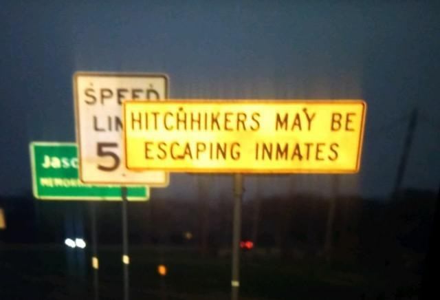 Street sign - SPEED LIN HITCHIKERS MAY BE 5 ESCAPING INMATES Jasc NEROR