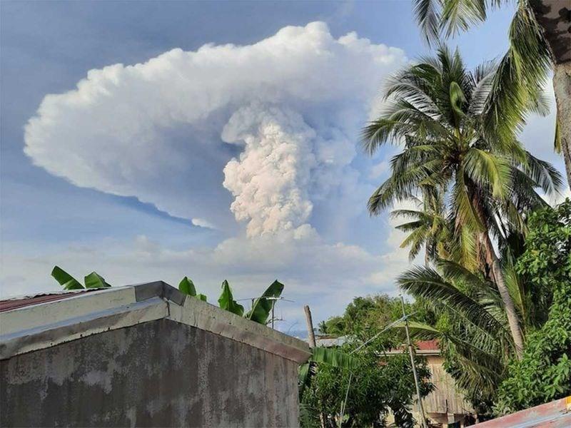 huge white ash could mushroom cloud in sky behind palm tree building