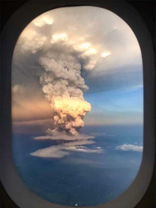 pillar of smoke from taal volcano seen through airplane window