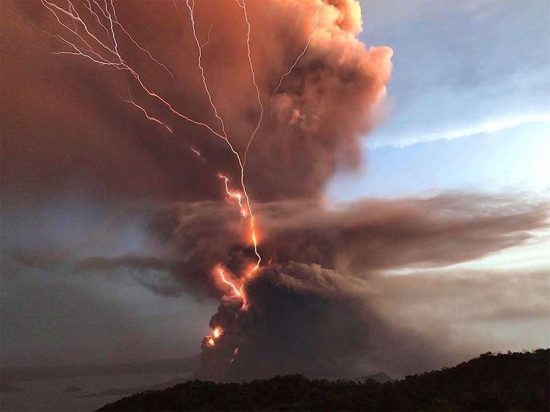 orange red smoke coming from taal volcano sky lightning