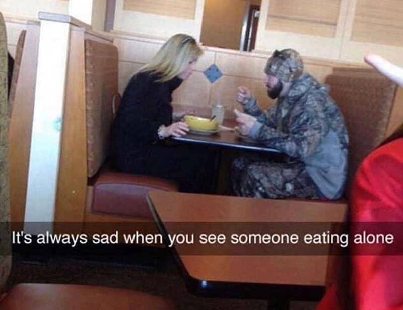 funny meme about woman eating alone, she's actually eating with a man completely dressed in camouflage.