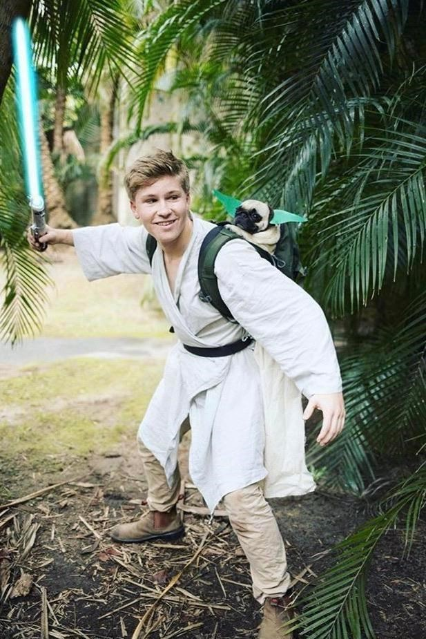 cosplay costume man dressed as luke skywalker from star wars training on planet daguba holding a light saber and a pug dog with long green ears strapped on his back like yoda