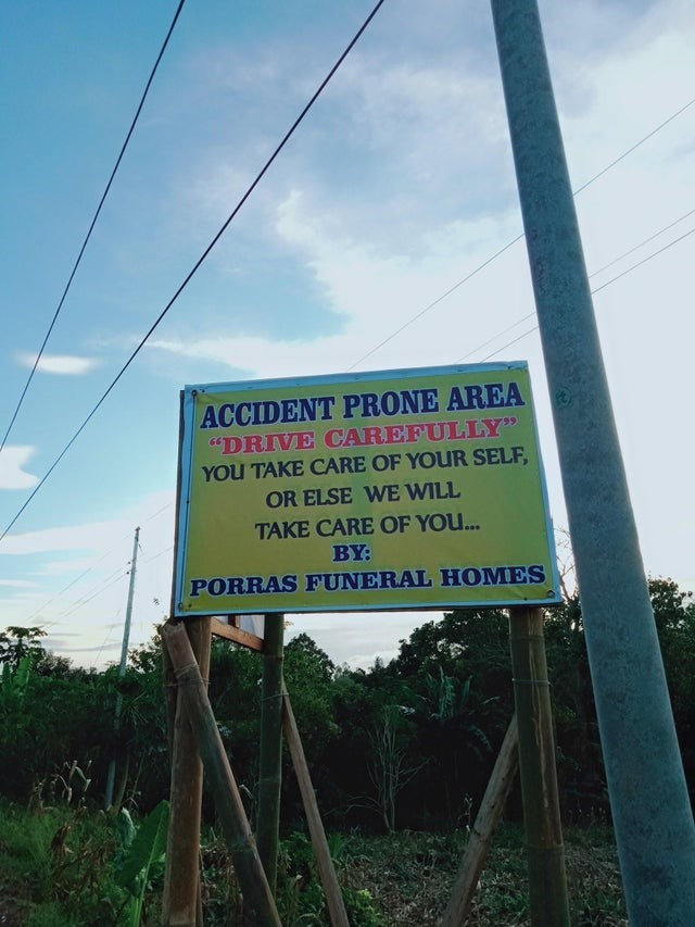 """Advertising - ACCIDENT PRONE AREA """"DRIVE CAREFULLY"""" YOU TAKE CARE OF YOUR SELF, OR ELSE WE WILL TAKE CARE OF YOU.. BY: PORRAS FUNERAL HOMES"""