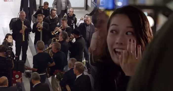 Danish band surprises their new Japanese conductor at the Danish airport with an ensemble flash mob