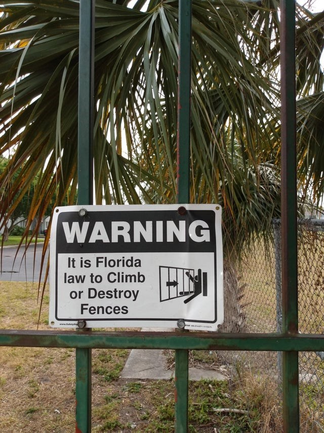 Street sign - WARNING It is Florida law to Climb or Destroy Fences wwww.atyt