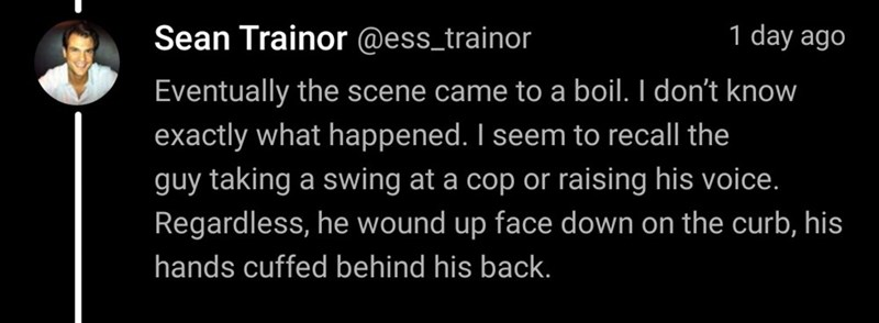 Text - Sean Trainor @ess_trainor 1 day ago Eventually the scene came to a boil. I don't know exactly what happened. I seem to recall the guy taking a swing at a cop or raising his voice. Regardless, he wound up face down on the curb, his hands cuffed behind his back.