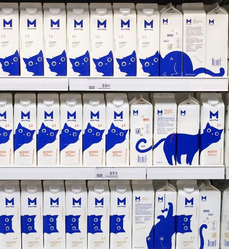 shelf of milk cartons with pictures of cats printed on them