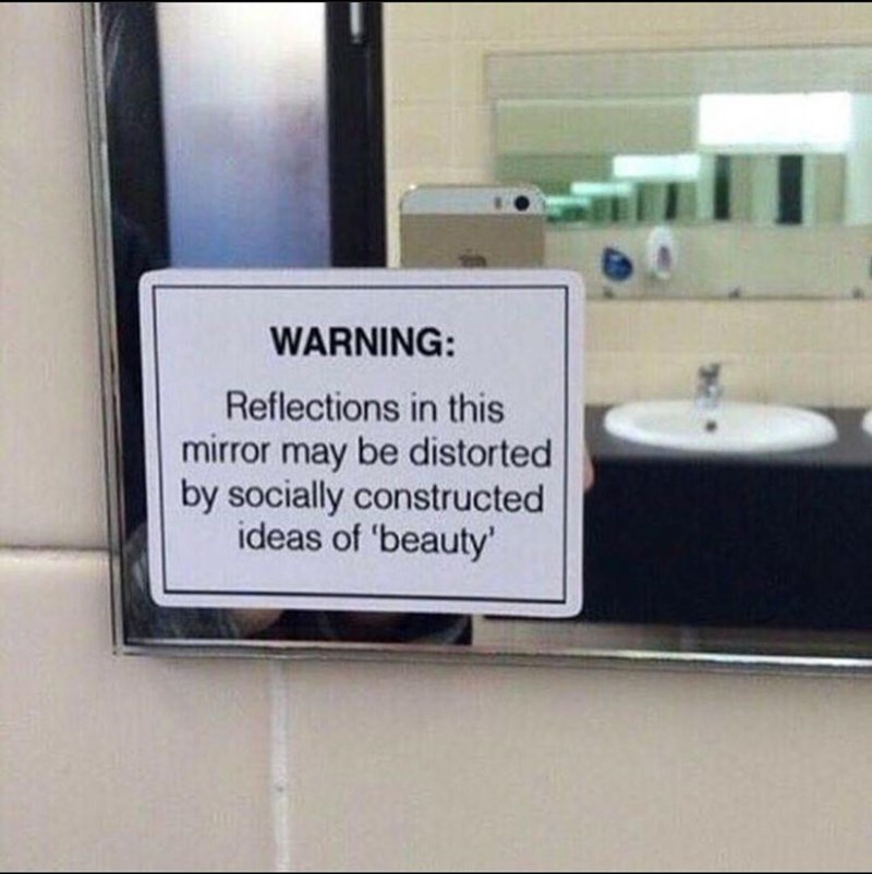 Text - WARNING: Reflections in this mirror may be distorted by socially constructed ideas of 'beauty'