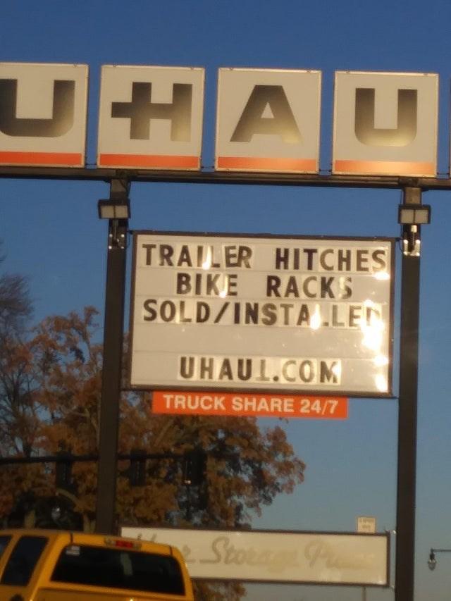 Street sign - TRAILER HITCHES BIKE RACKS SOLD/INSTA LEN UHAUL.COM TRUCK SHARE 24/7 StorP