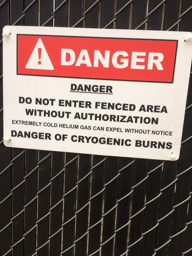 Text - A DANGER DANGER DO NOT ENTER FENCED AREA WITHOUT AUTHORIZATION EXTREMELY COLD HELIUM GAS CAN EXPEL WITHOUT NOTICE DANGER OF CRYOGENIC BURNS