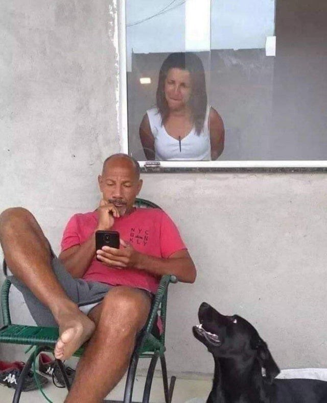List of funny pics and memes scraped off of r/funny from Reddit and trimmed off some of the fat - Cover pic is a man on his phone as his wife or GF look on from behind a window over his shoulder, with a dog looking questionably at the interaction, implying there might be a fight to break out between the two over what he is looking at online