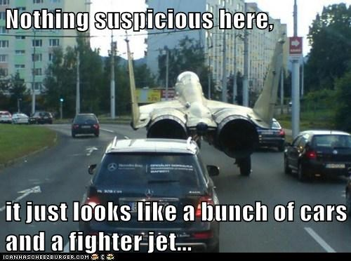 Nothing suspicious here,  it just looks like a bunch of cars and a fighter jet...