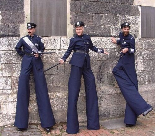police officers,long pants,stilt walkers,poorly dressed,g rated