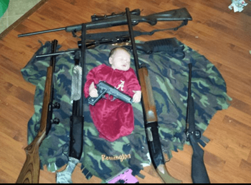 Bad Parenting of the Day: Baby Poses with Gun Collection