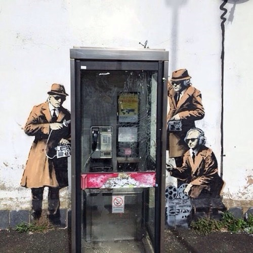 Street Art of the Day: This New Banksy Piece Depicts Agents Listening in at a Phone Booth