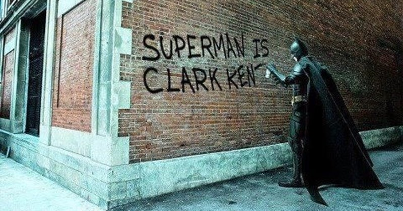 "Batman writing on a brick wall, ""Superman is Clark Kent"""